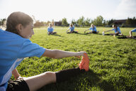 Middle school girl soccer team stretching at practice on sunny field - HEROF13373