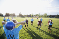 Middle school girl soccer team playing game on sunny field - HEROF13376