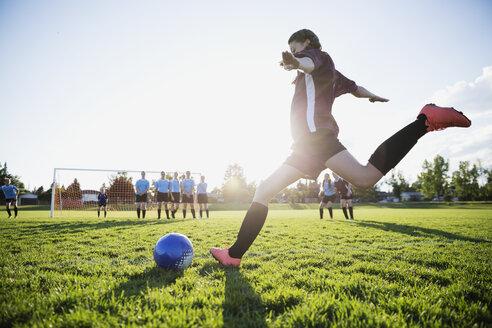 Middle school girl soccer player kicking free kick on sunny field - HEROF13379