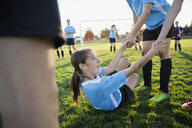 Middle school girl soccer players helping teammate up on field - HEROF13388