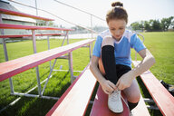 Middle school girl soccer player tying shoe on bleachers - HEROF13391