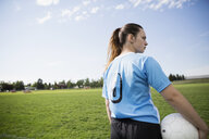 Middle school girl soccer player holding soccer ball on field - HEROF13394