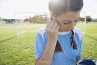 Middle school girl soccer player listening to music with headphones and mp3 player on sunny field - HEROF13397