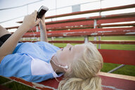 Middle school girl soccer player laying listening to music with headphones and mp3 player on bleachers - HEROF13406
