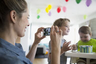 Mother with camera phone photographing baby son with birthday cake - HEROF13424