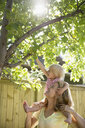 Mother helping daughter reaching for apples on tree in sunny backyard - HEROF13442