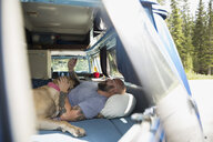 Man with dog relaxing and texting with cell phone in camper van - HEROF13454