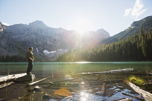 Man standing on rock enjoying sunny view of remote mountains and lake - HEROF13460