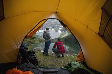 Men looking at lake view outside of camping tent - HEROF13463