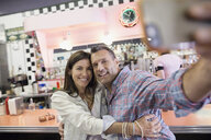 Mature couple taking selfie in soda fountain shop - HEROF13478