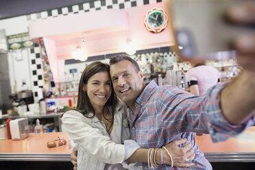 Mature couple taking selfie in soda fountain shop - HEROF13478