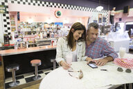 Mature couple drinking milkshake and reviewing map in soda fountain shop - HEROF13481