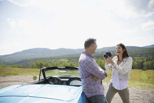 Mature couple with camera at convertible at rural overlook - HEROF13487