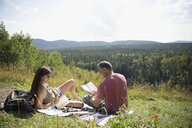 Mature couple reading books on blanket in sunny remote grass - HEROF13493