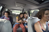 Mother driving daughters using cell phones in back seat of SUV - HEROF13499