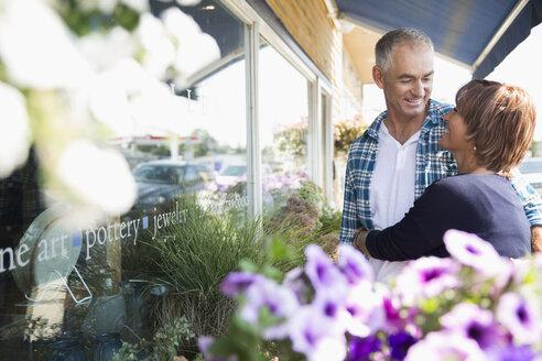 Mature couple hugging at flower shop storefront - HEROF13517