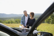 Mature couple looking at map on automobile hood at sunny rural overlook - HEROF13520