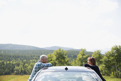 Mature couple talking over car at sunny rural overlook - HEROF13529