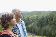 Mature couple hiking looking at remote rural view - HEROF13532