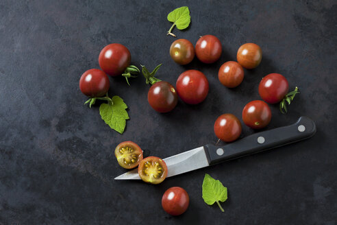 Whole and sliced risp tomatoes 'Black Cherry', leaves and kitchen knife on dark ground - CSF29216
