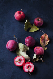 Sliced and whole red-fleshed apples on dark ground - CSF29291