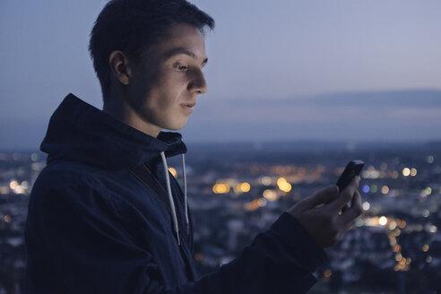 junger Man mit Smartphone bei Dämmerung mit den Lichtern einer Stadt im Hintergrund, Wartberg, Deutschland, Baden-Würtemberg, Heilbronn - GCF00240