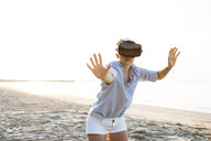 Thailand, woman using virtual reality glasses on the beach in the morning light - HMEF00186