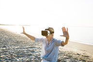 Thailand, woman using virtual reality glasses on the beach in the morning light - HMEF00189