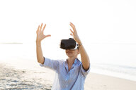 Thailand, woman using virtual reality glasses on the beach in the morning light - HMEF00192