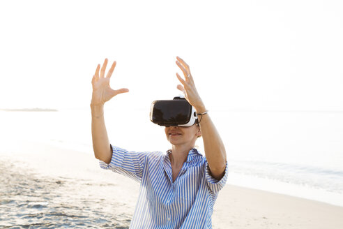 pretty blonde woman using virtual 3D glasses on a beach in Thailand, in the morning light - HMEF00192