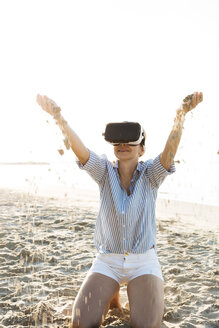 Thailand, woman using virtual reality glasses on the beach in the morning light - HMEF00195
