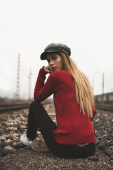 Portrait of fashionable young woman wearing cap and red pullover outdoors - ACPF00402