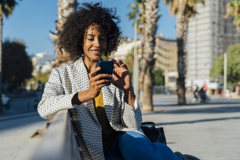 Beautiful woman sitting on a bench in the city, takig pictures with her smartphone - BOYF01320