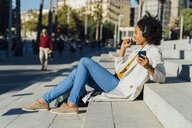 Beautiful woman sitting on stairs in the city, using smartphone, listening music with headphones - BOYF01332