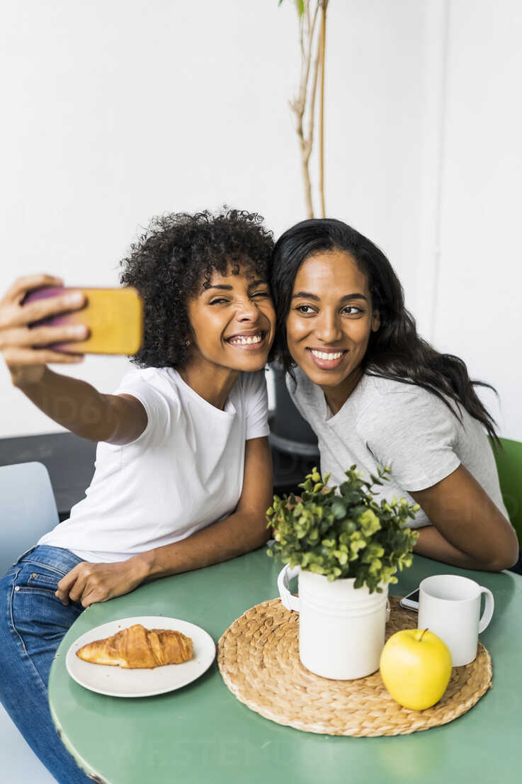 Two happy girlfriends sitting at table taking a selfie - GIOF05630 - Giorgio Fochesato/Westend61