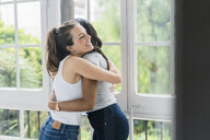 Two happy girlfriends hugging at the window - GIOF05636