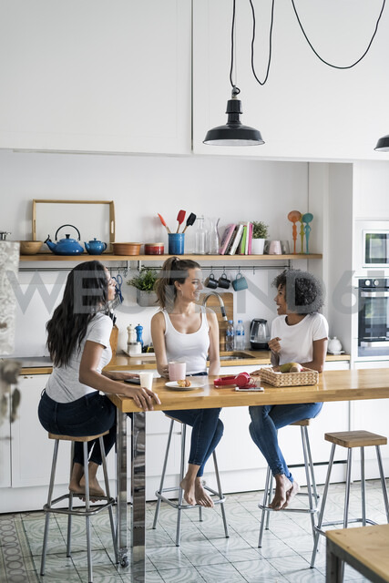 Three happy women sitting at kitchen table at home socializing - GIOF05645 - Giorgio Fochesato/Westend61