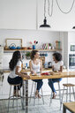 Three happy women sitting at kitchen table at home socializing - GIOF05645