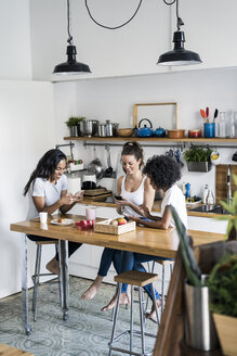 Three happy women sitting at kitchen table at home using cell phones - GIOF05648