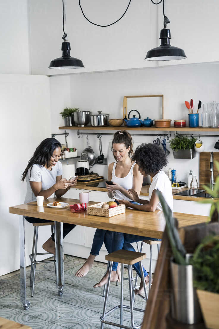 Three happy women sitting at kitchen table at home using cell phones - GIOF05648 - Giorgio Fochesato/Westend61