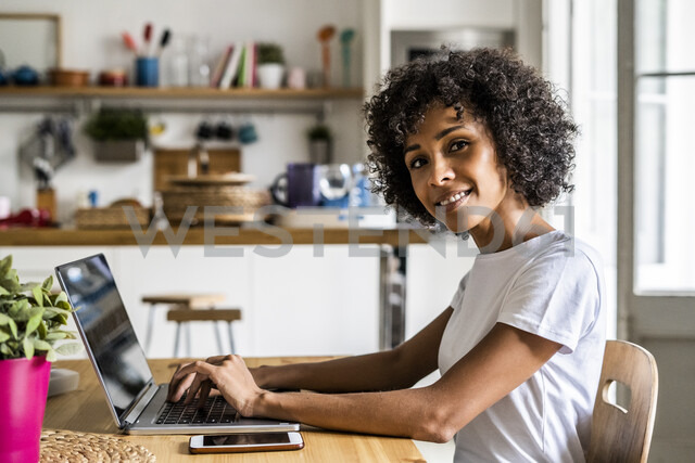 Portrait of smiling woman using laptop at table at home - GIOF05654