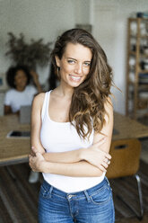 Portrait of smiling woman at home with friends in background - GIOF05663