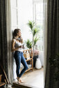 Woman with cup of coffee and headphones standing in doorframe at home - GIOF05666