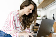 Smiling woman using laptop in kitchen at home - GIOF05678