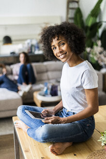 Portrait of smiling woman with tablet on table at home with friends in background - GIOF05681