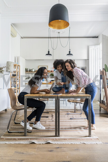 Three happy women with digital devices on table at home - GIOF05687