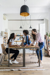 Three happy women talking at table at home - GIOF05690