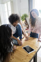 Three happy women looking at cell phone on table at home - GIOF05696