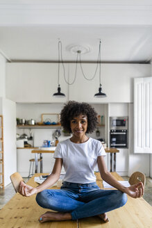 Portrait of smiling woman in yoga pose on table at home - GIOF05699