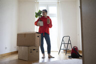 Young woman moving into her new home, carrying a potted plant - MOEF01973